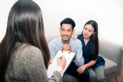 couple sitting on couch talking to therapist